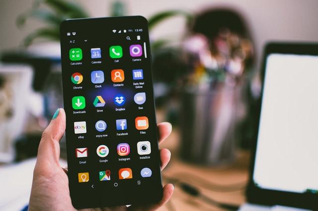 Hombre con un celular en la mano con aplicaciones de entretenimiento